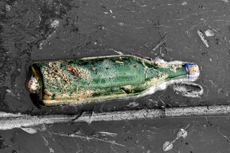 une bouteille flotte à la surface d'une eau sale, bottle, photo dominique houcmant, goldo graphisme