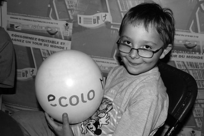 un gamin joue avec un ballon de baudruche aux couleurs ECOLO, photo dominique houcmant, goldo graphisme
